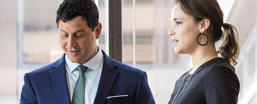 man in a suit and woman wearing a dress in an office building