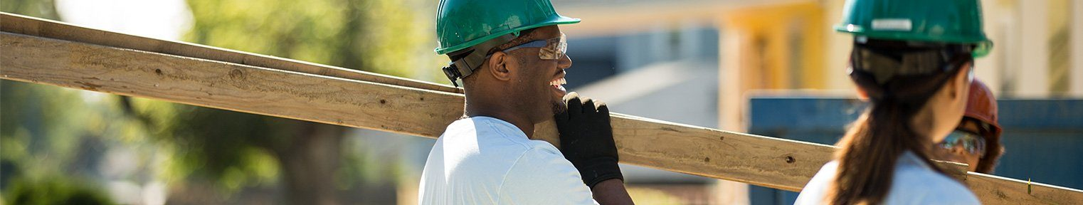man in a hard hat carrying lumber