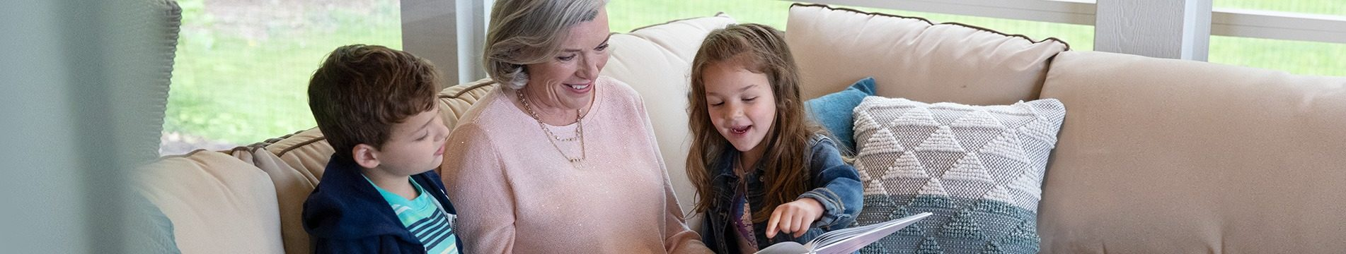A grandmother reading to her two grandchildren on a couch